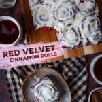 A single red velvet cinnamon rolls on a plate, with the remaining cinnamon rolls on a cutting board, surrounded by two mugs of tea.
