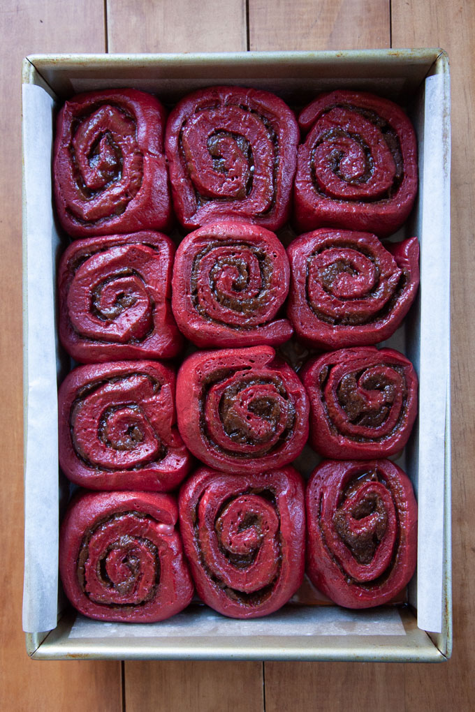 Puffy and risen red velvet cinnamon rolls ready to be baked.