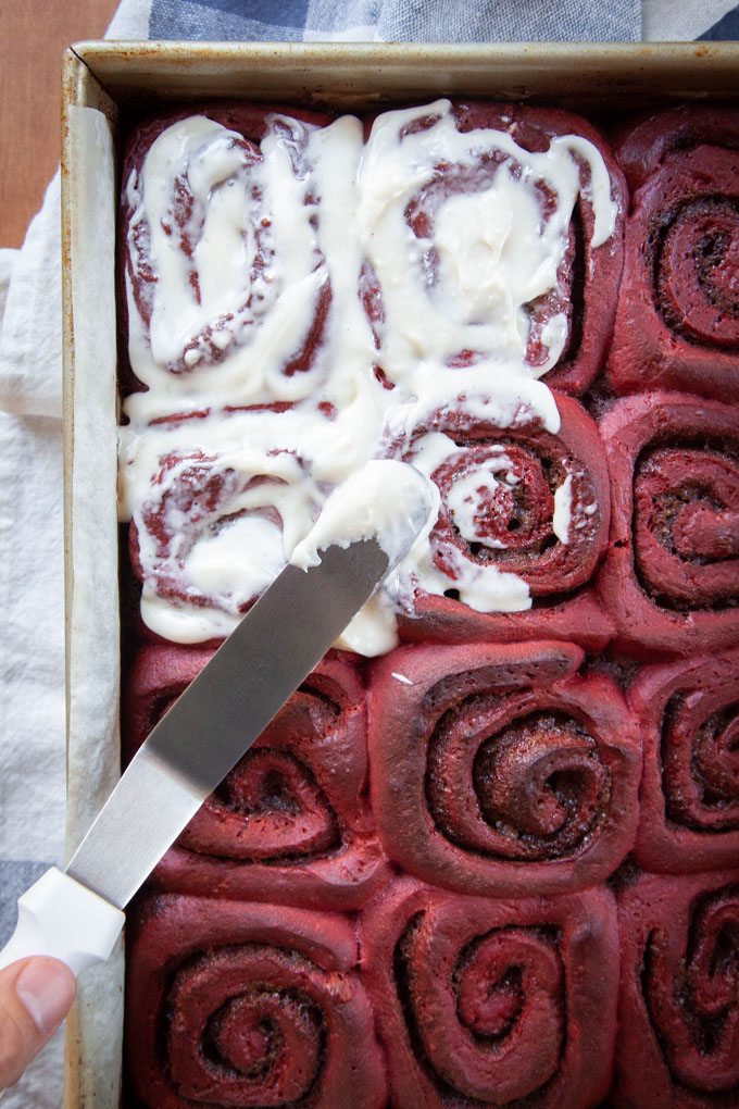 Frosting red velvet cinnamon rolls with cream cheese frosting.
