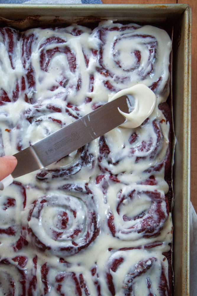 Spreading more cream cheese frosting over the red velvet cinnamon rolls.