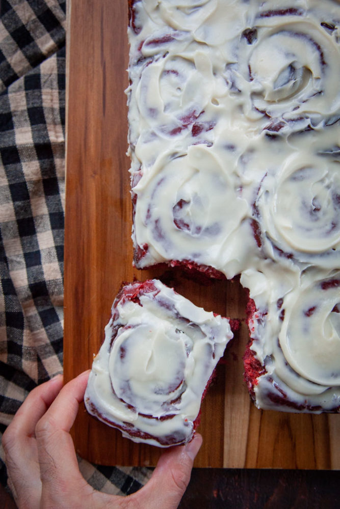 A hand reaching for a red velvet cinnamon bun