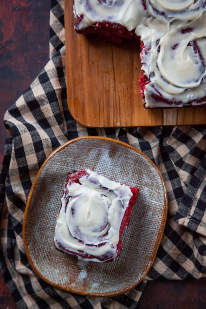 a red velvet cinnamon roll on a plate next to a cutting board with the remaining cinnamon rolls.
