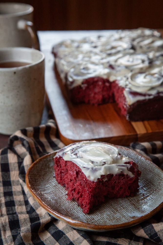 A red velvet cinnamon roll on a plate, with the remaining cinnamon rolls behind it, along with two mugs of tea.