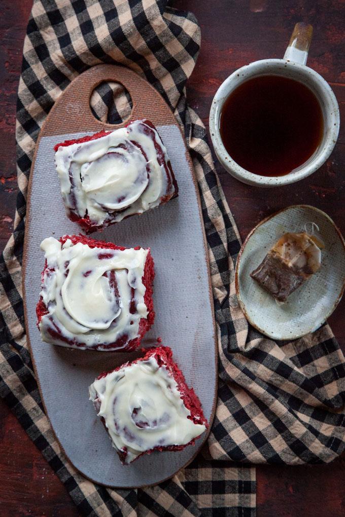 Three red velvet cinnamon rolls on a ceramic cheeseboard next to a mug of tea.