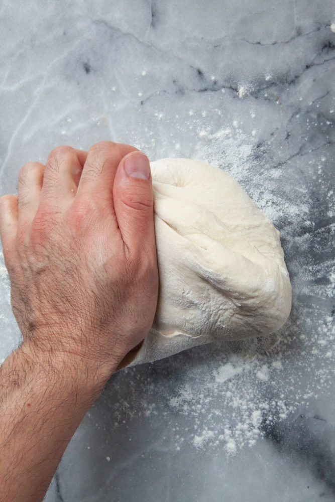 Kneading pizza dough on a marble counter.