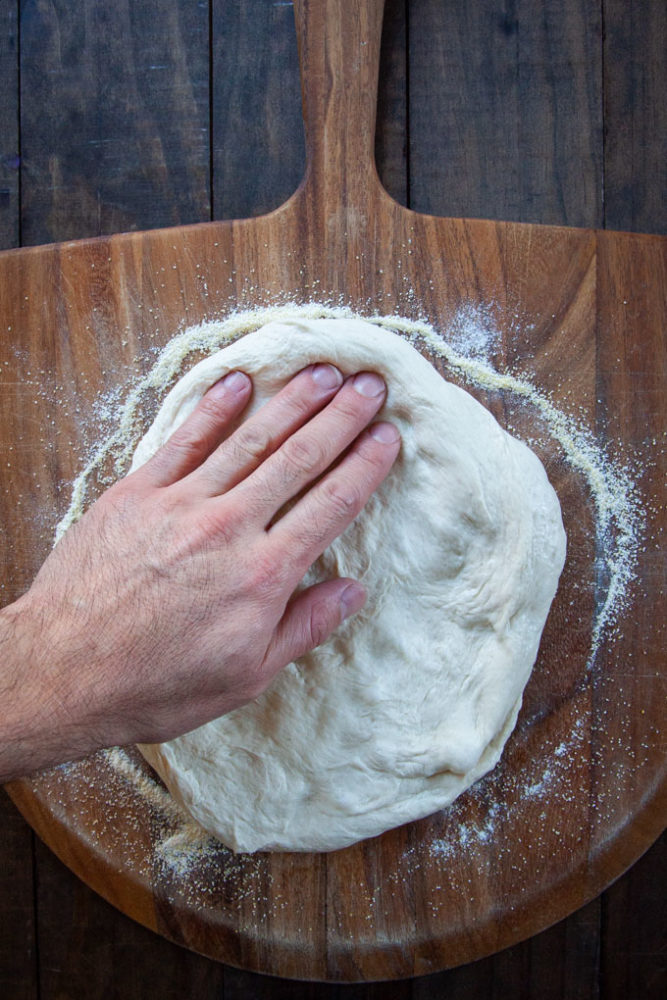 Stretching the dough on a pizza peel.