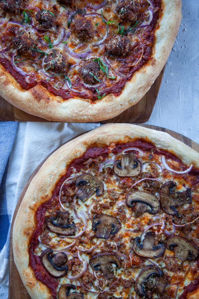 two pizzas on a pizza peels.