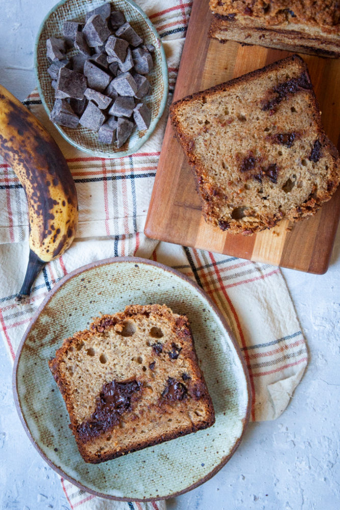 slice of sourdough banana bread on a plate next to the loaf and ingredients.
