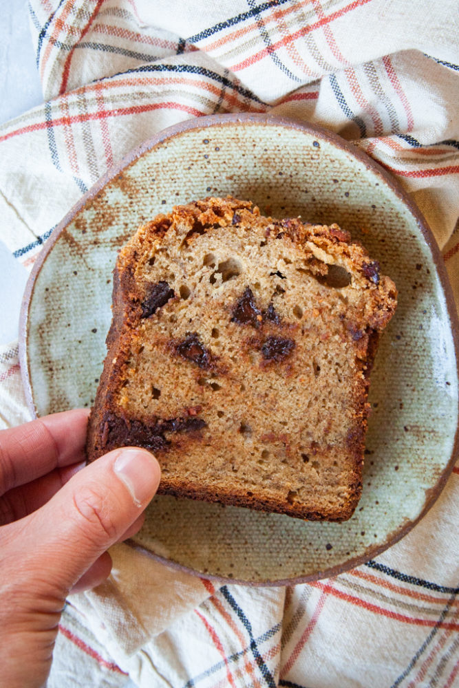 A hand reaching for a slice of sourdough banana bread on a plate.