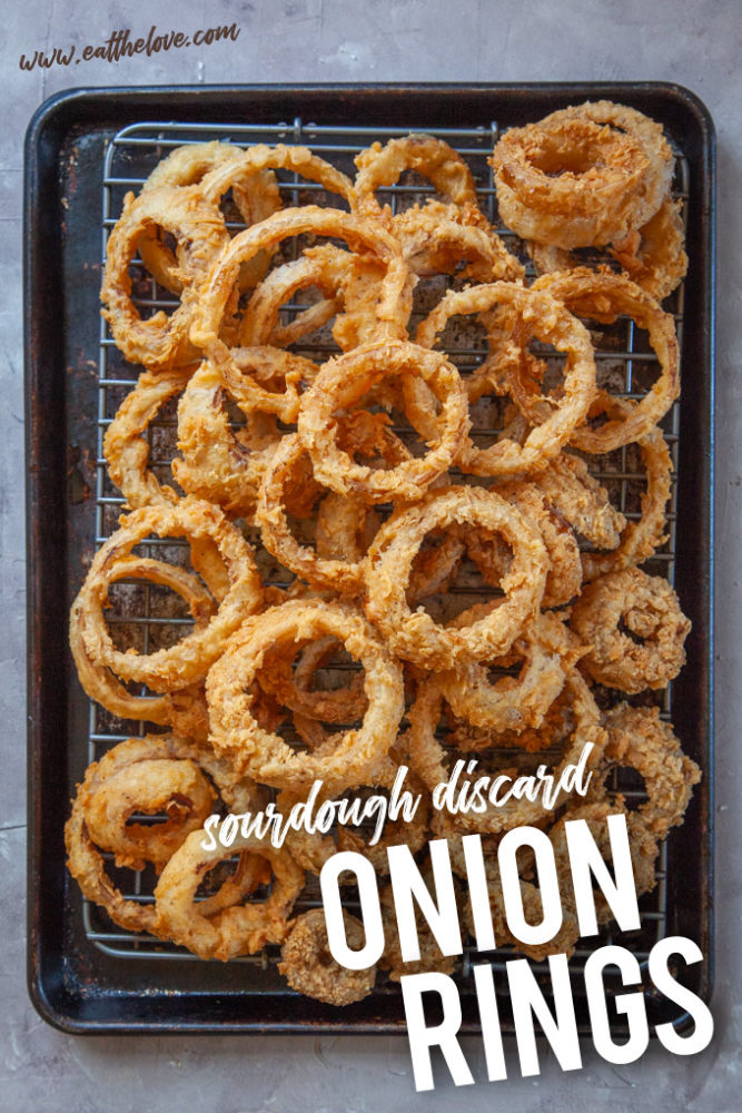 Onion Rings coated with sourdough discard piled up on a sheet pan.