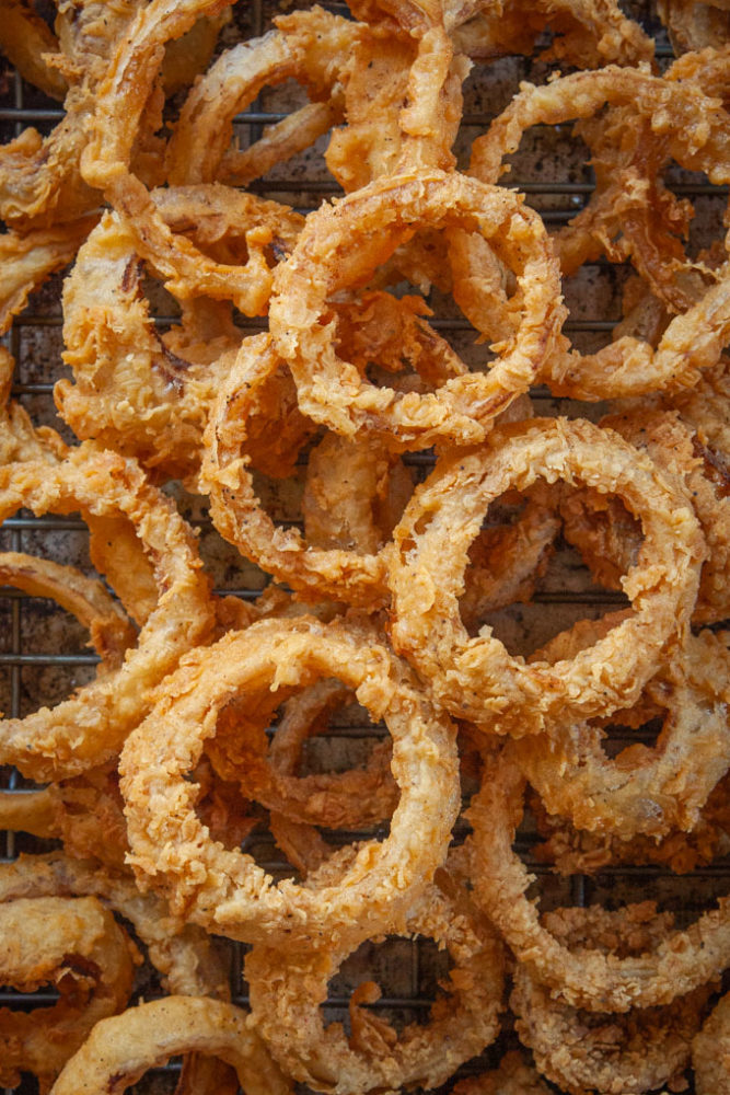Sourdough onion rings piled up on a baking sheet.