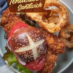 Pork tenderloin sandwich with a pretzel bun on a plate with onion rings.