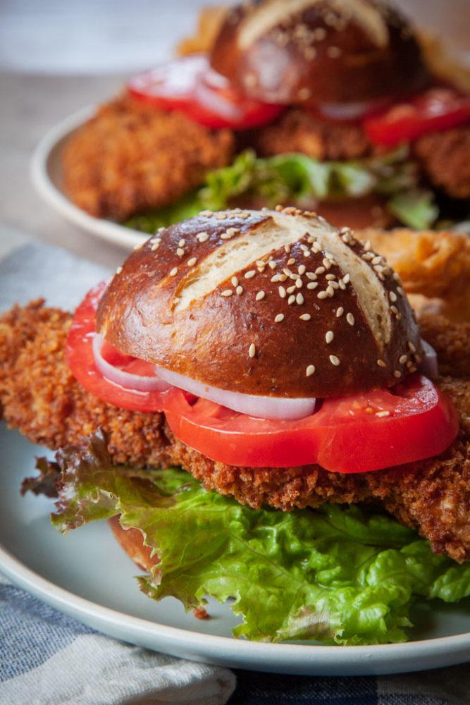 Pork tenderloin sandwiches with pretzel buns on plates
