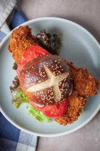 Pork tenderloin sandwich with a pretzel bun on a plate.
