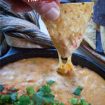 A chip being dipped into some homemade queso cheese dip.