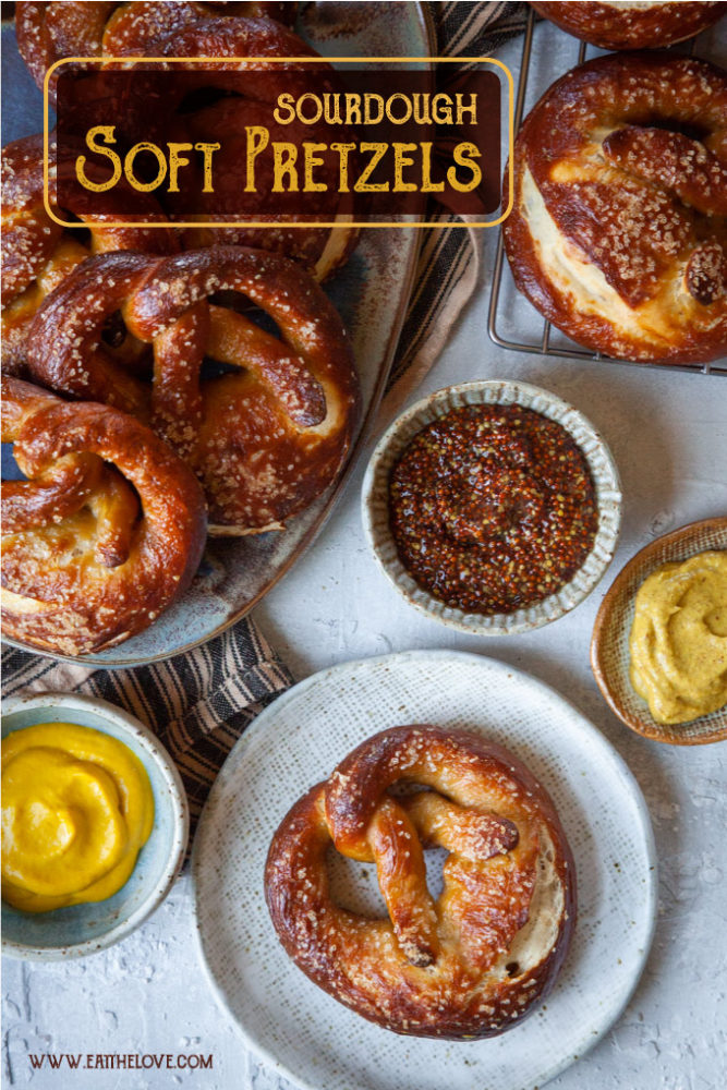 Sourdough pretzels on a plate surrounded by mustards for dipping.