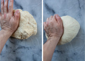 a hand kneading dough on a marble surface.