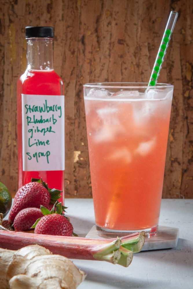 a glass of strawberry rhubarb soda with a bottle of homemade syrup and the ingredients next to it.