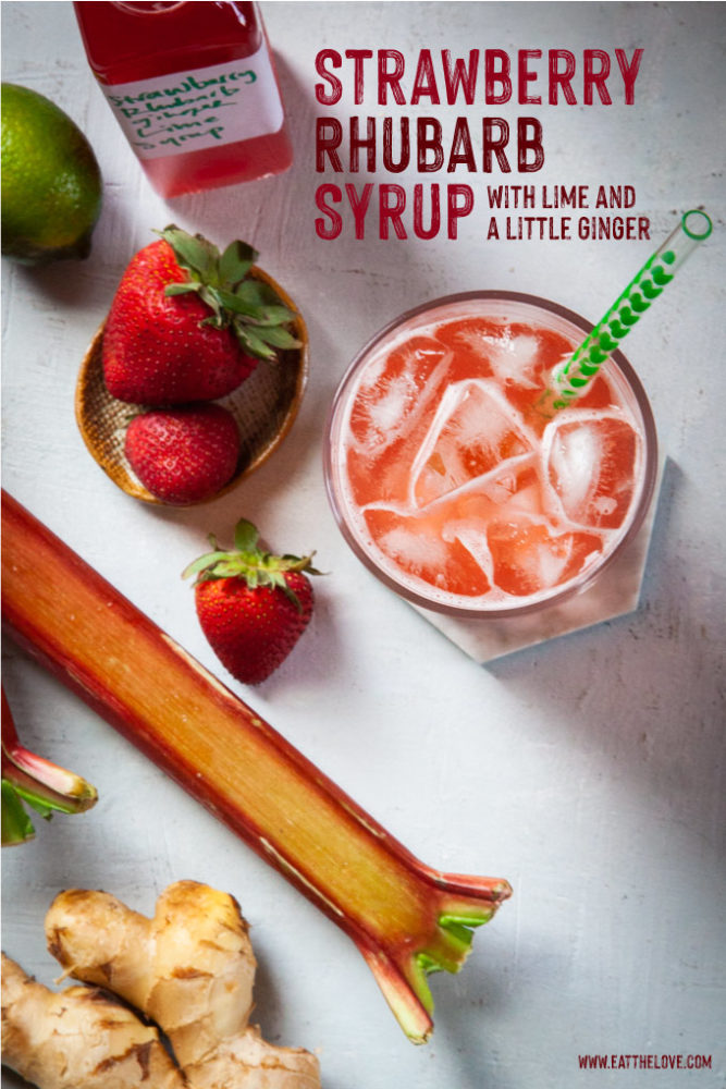 a cup of strawberry rhubarb soda made with homemade syrup surrounded by strawberries, rhubarbs, ginger and lime.