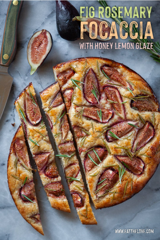 Fig rosemary focaccia cut up on a marble surface next to a cut fit and a knife.