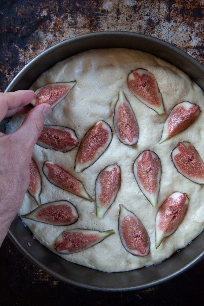 A hand pressing cut figs into the focaccia dough.