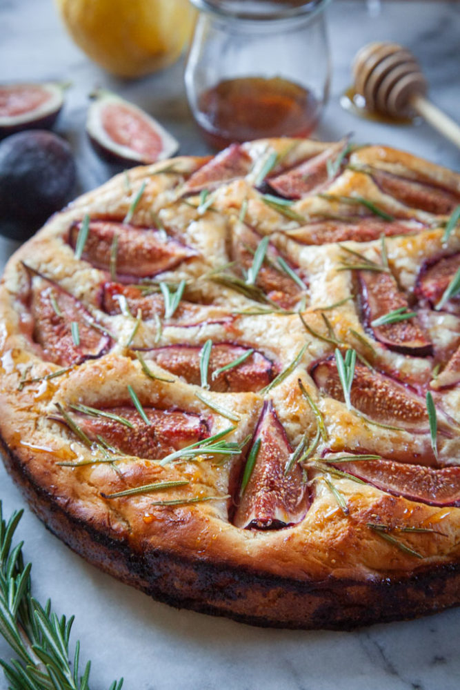 fig rosemary focaccia on a marble surface surrounded by ingredients for the dish.