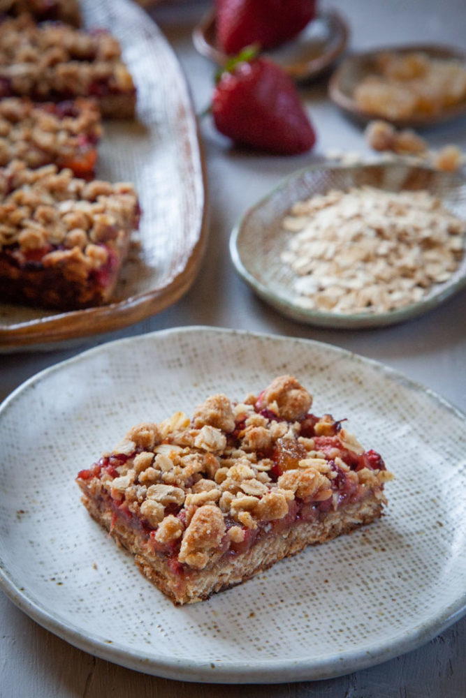 a single strawberry oatmeal bar on a plate, with more bars behind it.