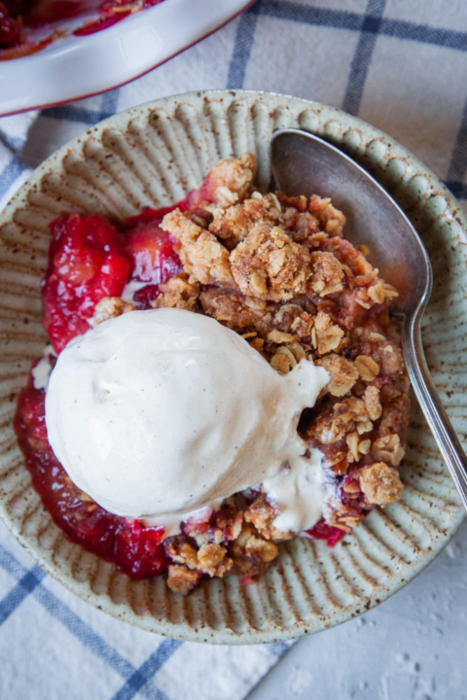 a bowl of plum crisp with vanilla ice cream on top.