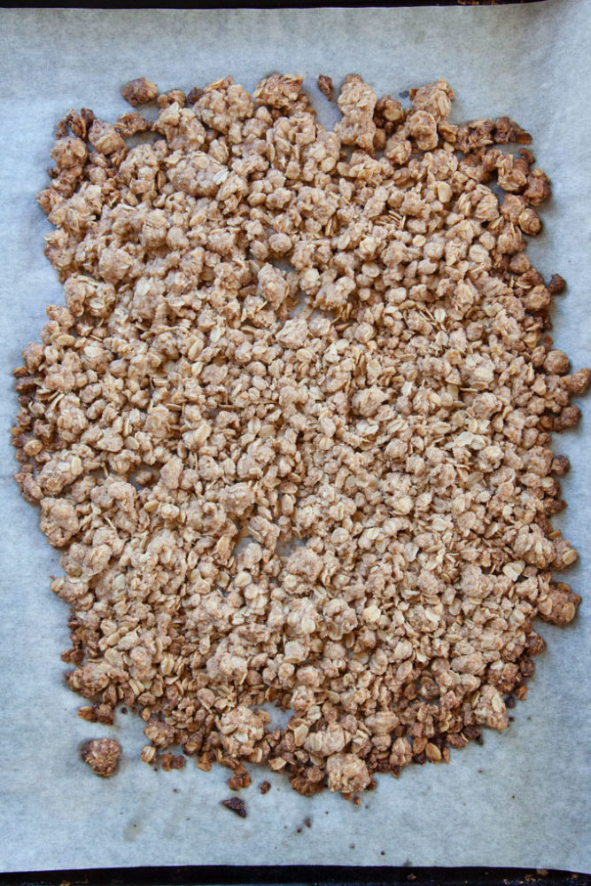 Baked crisp topping on parchment paper lined baking sheet.