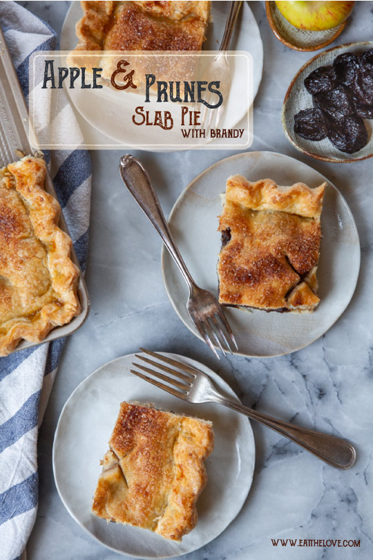 Slices of apple slab pie with prunes and brandy on plates, with a small plate of prunes and an apple next to them.