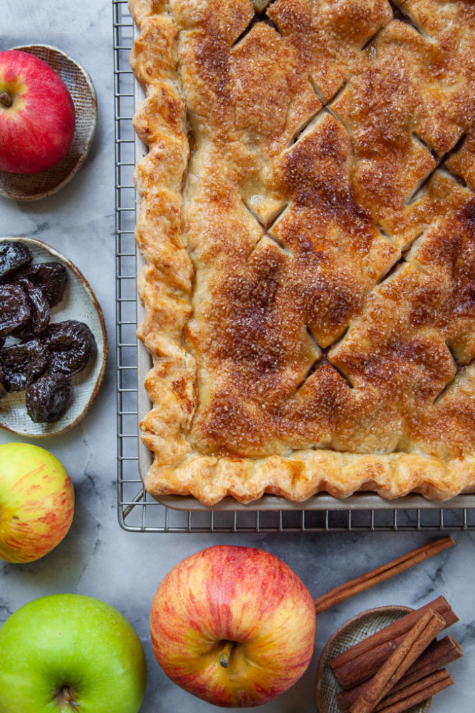 An apple and prunes slab pie next to apples, prunes and sticks of cinnamon