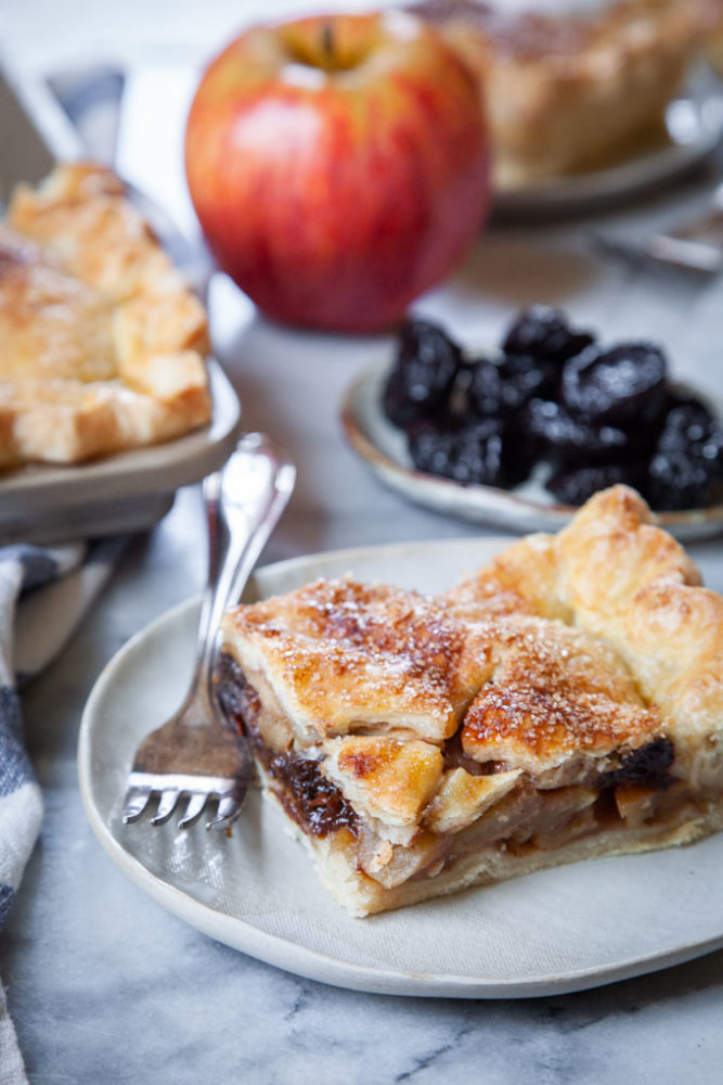 A slice of apple slab pie on a plate, with apples and prunes behind it, along with the remaining pie to the side.