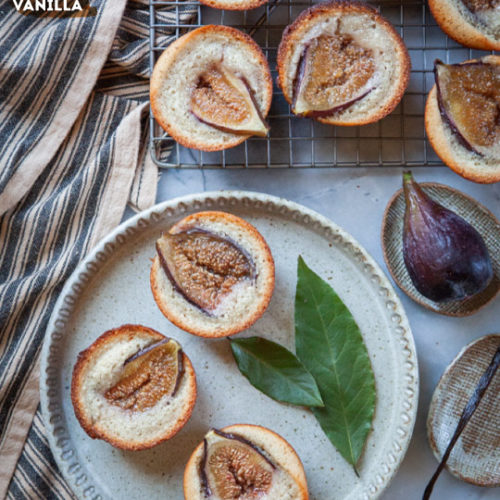 Fig financiers on a plate and wire cooling rack, surrounded by bay leaves, fresh figs and vanilla bean pod.