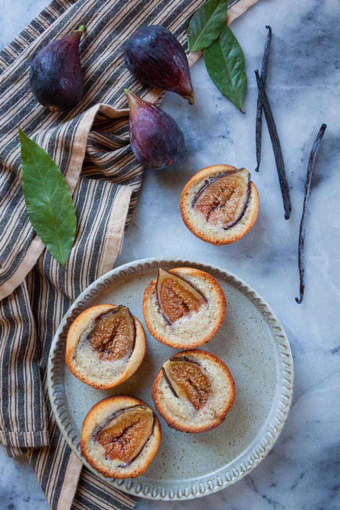 Figs, bay leaves, vanilla bean pods and fig financiers on a plate.