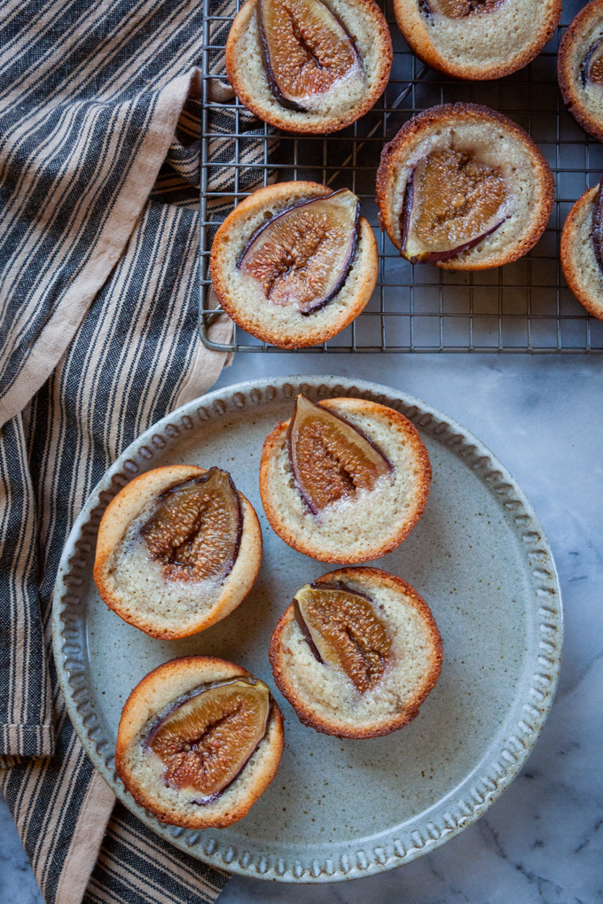 Fig financiers on a plate, next to more fig financiers on a wire cooling rack.