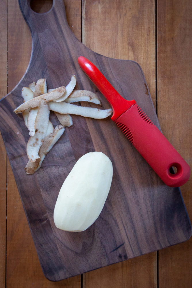A small russet potato peeled on a cutting board.