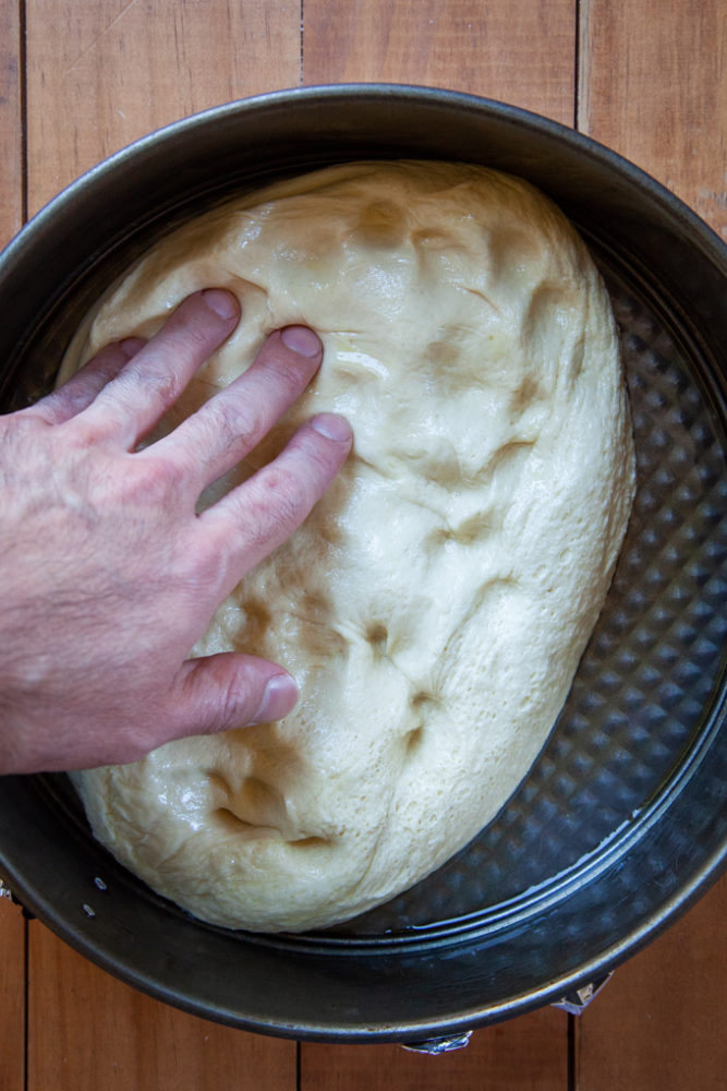 Pressing the focaccia dough out into the pan.