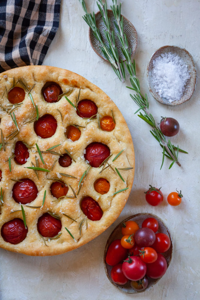 Tomato rosemary focaccia on a table next to a small plate of cherry tomatoes, a sprig of fresh rosemary and flaky salt.