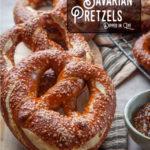 Several Bavarian pretzels on a cutting board.