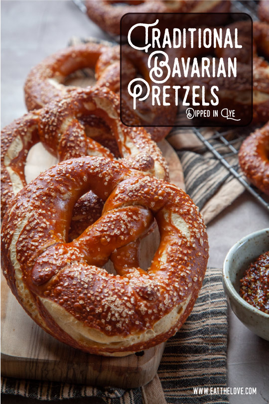 Several Bavarian pretzels on a cutting board.