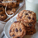 Oatmeal raisin cookies stacked on a plate, with a pile of cookies and a glass of milk in the background.