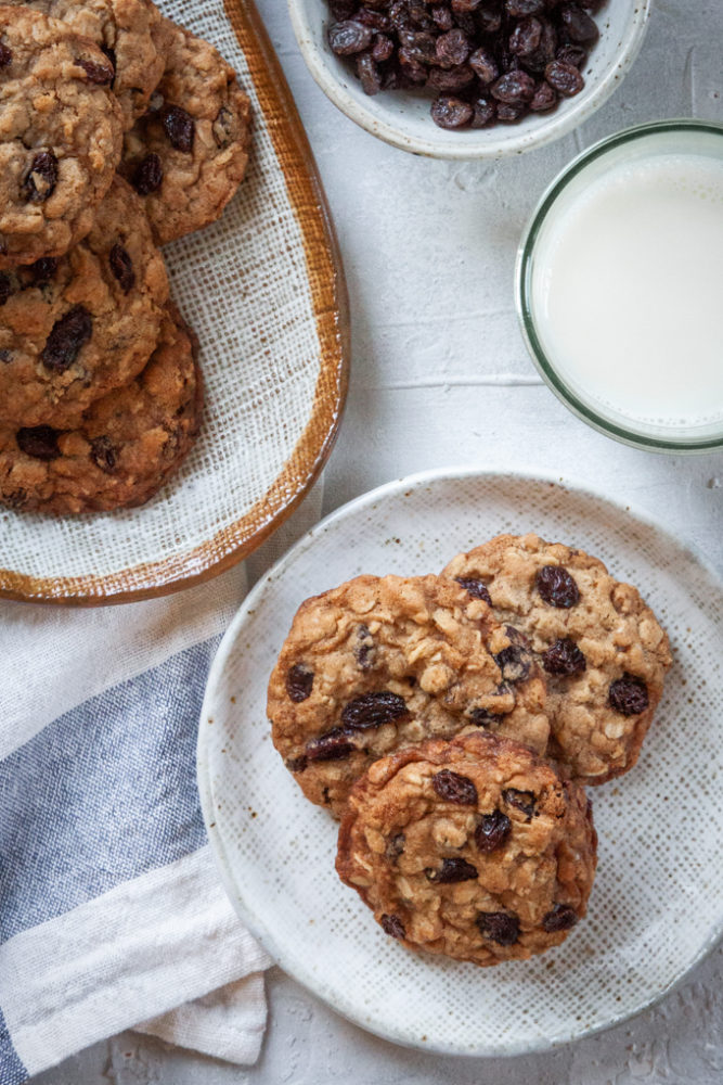A plate of oatmeal cookies with a glass milk and a bowl of raisins next to it.