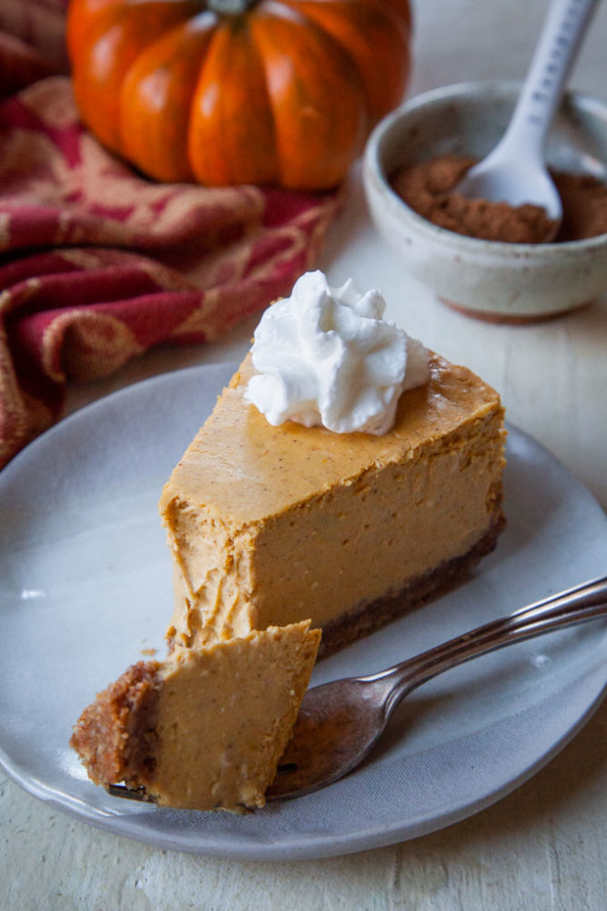 A slice of pumpkin cheesecake with whipped cream on it and a bowl of pumpkin pie spice and a pumpkin in the background.