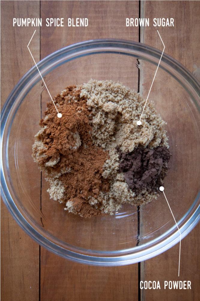 Ingredients for the filling, including pumpkin spice, brown sugar and cocoa in a bowl.