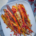 Roasted rainbow carrots with za'atar spices and drizzled with pomegranate molasses and seeds on a white serving plate.
