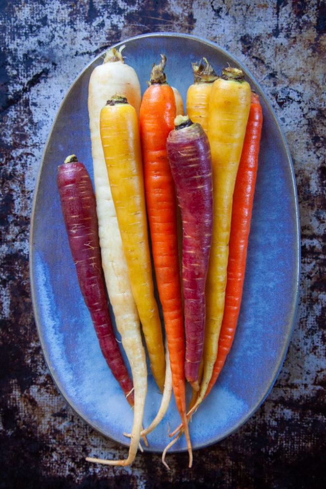 Rainbow carrots on a blue plate.