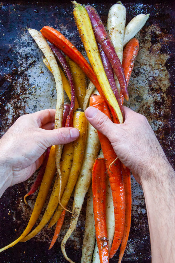 Hands tossing carrots with olive oil and spices.