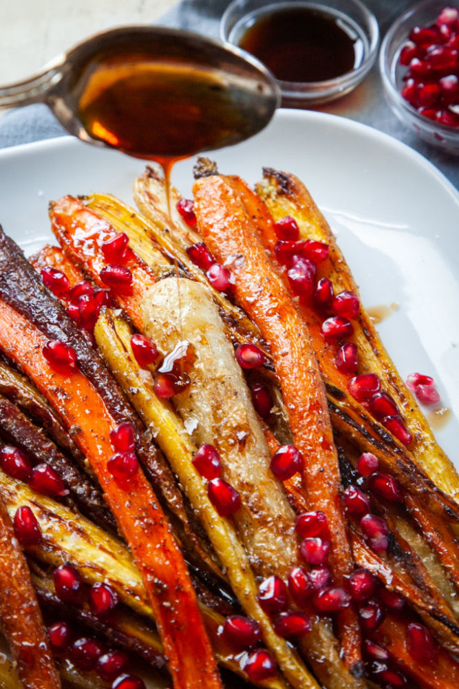 A spoon drizzling pomegranate molasses over roasted carrots.