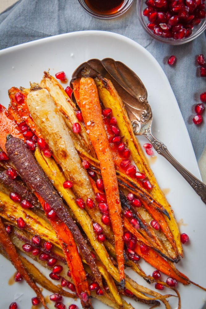 Roasted carrots with pomegranate seeds on a serving plate with a serving spoon.