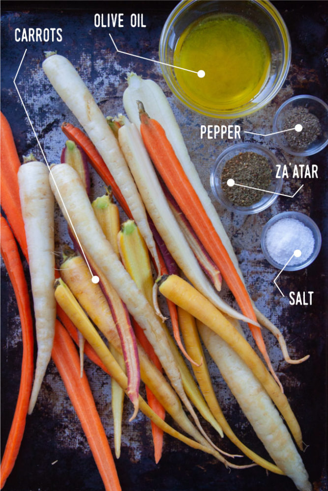 Rainbow carrots sliced lengthwise on a rimmed baking sheet with small bowls filled with olive oil, salt, pepper and za'atar spices.